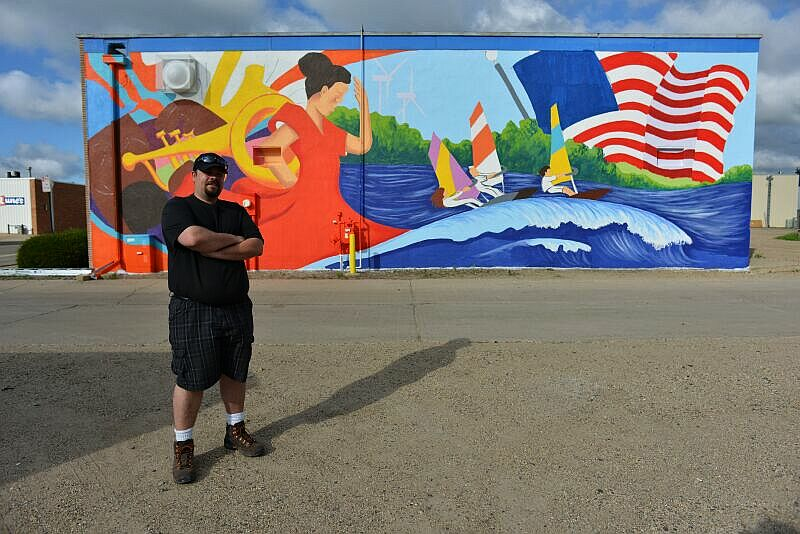 Artist Shawn McCann in front of the mural he created for the event (credit: Ron Kern)